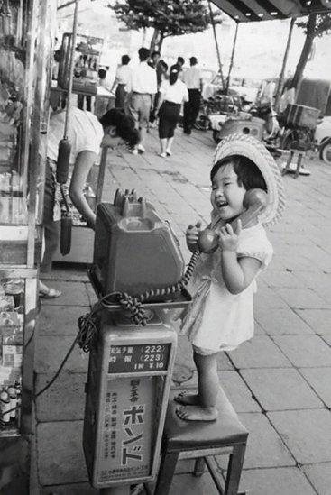 Una bambina si diverte facendo finta di parlare al telefono, Giappone, 1958. Fotografia di Marc Riboud