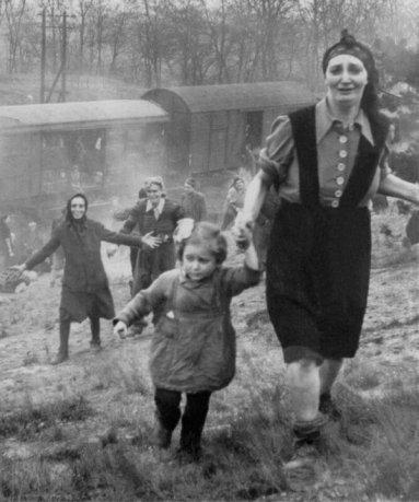 Profughi ebrei diventano consapevoli del fatto che hanno appena stati liberati, aprile 1945. Fotografia del Maggiore Clarence Benjamin