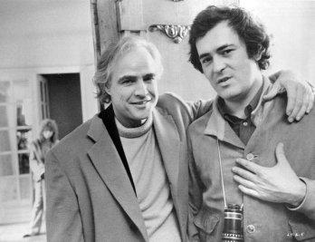 "Marlon Brando e Bernardo Bertolucci sul set di ""Ultimo tango a Parigi"". Sullo sfondo, Maria Schneider. 1972"