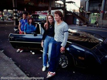 Due coppie adolescenti stanno con orgoglio accanto a una appariscente Trans Am a Brooklyn, Estate 1982