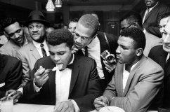 Muhammad Ali mangia alla festa per aver battuto Sonny Liston per il titolo dei pesi massimi. Accanto a lui anche Malcolm X