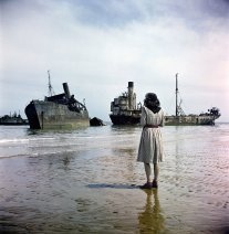 Una donna guarda le navi in rovina utilizzate nella battaglia del D-Day in Normandia. Fotografia di David Seymour 1947