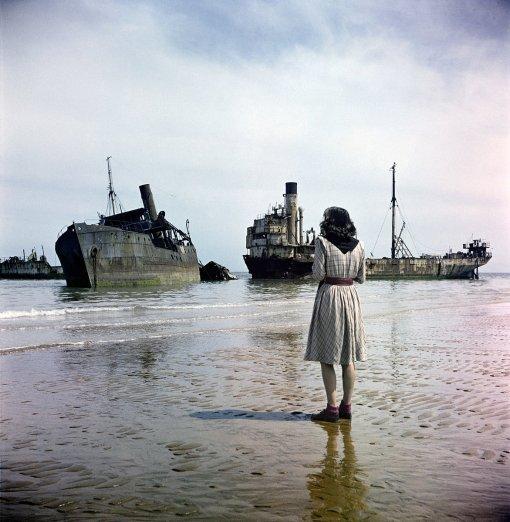 Una donna guarda le navi in rovina utilizzate nella battaglia del D-Day in Normandia. Fotografia di David Seymour 1947