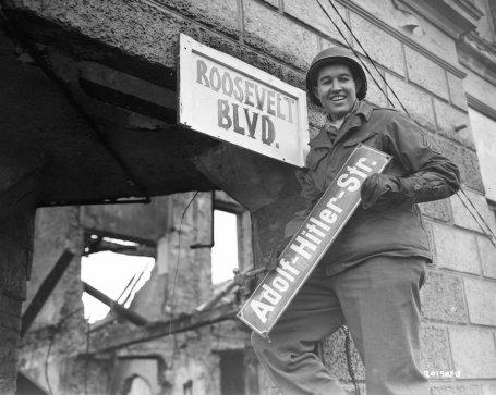 Il sergente americano George A. Kaufman, sostituisce un cartello 'Adolf Hitler S.', Germania, 1945. Fotografia dai National Archives