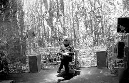 Andy Warhol seduto su una sedia alla Factory con la tela di Jacqueline Kennedy, le scatole Brillo e la parete d'argento. New York NY US 1964 Billy Name / NOvoWorks