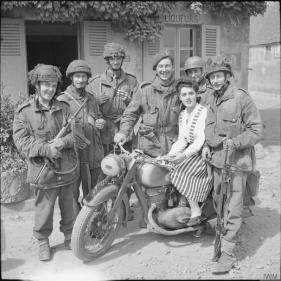 Truppe britanniche in posa con una ragazza francese su una moto tedesca requisita, Normandia 1944