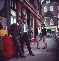 ragazzi che flirtano fuori dal J. Mendel & Sons, Londra, 1960