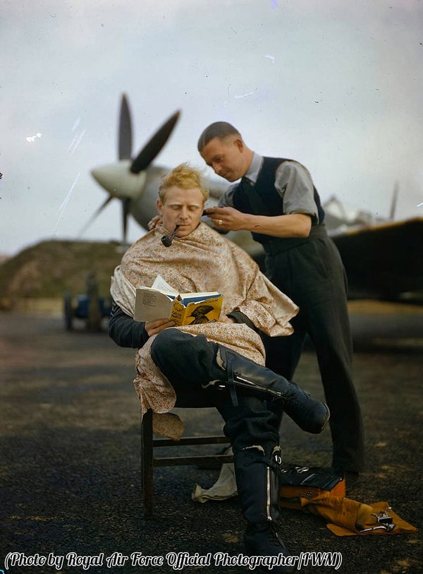 Il pilota di RAF Francesco Mellersh si fa tagliare i capelli e legge Greenmantle. Fotografia di John Buchan. Essex, Inghilterra 1942