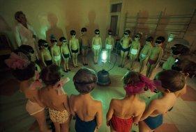 Bambini in cerchio attorno a una lampada a raggi ultravioletti per ottenere una dose di vitamina D a Murmansk, Unione delle Repubbliche Socialiste Sovietiche, agosto 1977