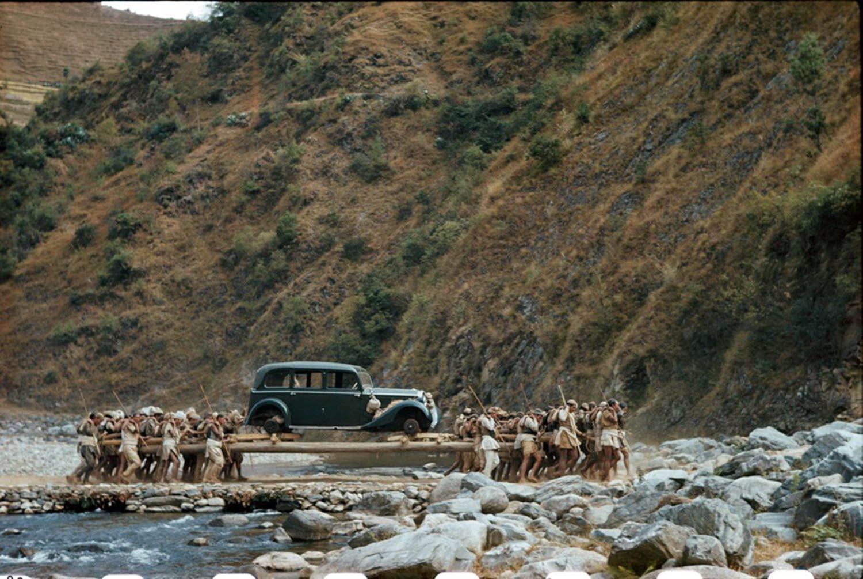 Facchini trasportano una macchina su lunghi pali in un ruscello in Nepal, 1948