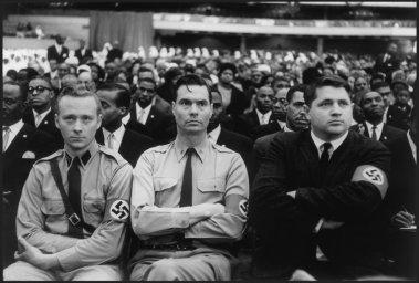 Il comandante del partito nazista americano George Lincoln Rockwell, affiancato da due membri del partito, ascolta il discorso di Malcolm X in un summit della nazione islamica presso la Uline Arena
