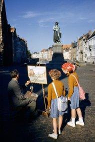 Ragazze guardano un artista che riproduce la statua di un artista fiammingo a Bruges, in Belgio, maggio 1955