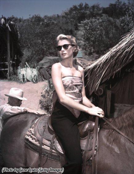 Grace Kelly a cavallo sul set di un film, probabilmente 'Mogambo', circa 1953