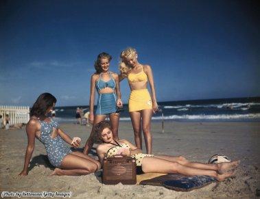 Modelle in costume da bagno mostrate mentre ascoltano la radio in spiaggia, circa 1940