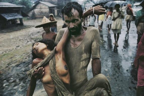 Un rifugiato porta la moglie colpita dal colera durante la guerra del Bangladesh, 1971