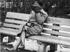 """Una donna ebrea che nasconde il volto seduta su una panchina marcata """"solo per ebrei"""", Austria 1938"""
