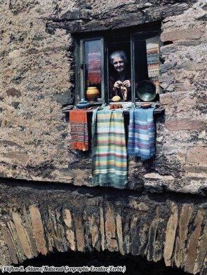 Una donna si affaccia fuori dalla finestra della sua casa sul ponte ad Ambleside, Lake District, Cumbria, Inghilterra 1928