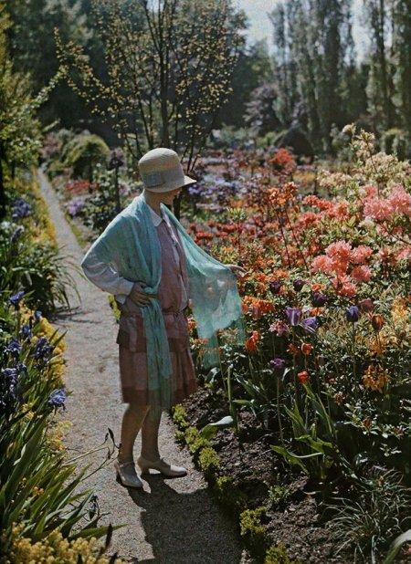 Una giovane donna ammira i fiori in un giardino a Baden in Germania, Giugno 1928