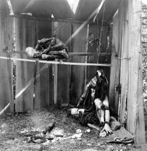 Uomo Kwakwaka'wakw fa affumicare la mamma su fumo e brace di fuoco, 1910