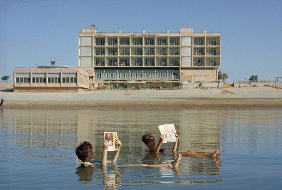 Bagnanti leggono vicino al litorale, mentre galleggiano nel Mar Morto, dicembre 1964
