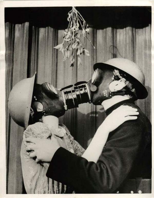 Coppia con maschere antigas si bacia sotto il vischio. Seconda guerra mondiale