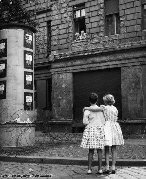 Due ragazze della Germania occidentale parlano con i propri nonni nella zona orientale, separati da una barriera di filo spinato, 1961
