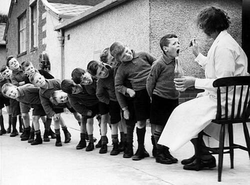 Bambini in fila per la loro dose settimanale di olio di pesce, 1960