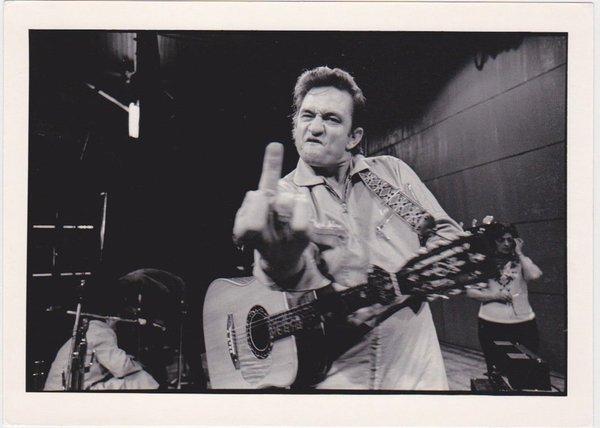 Johnny Cash mostra il dito medio durante la sua performance al carcere di San Quentin, 1969. Fotografia di Jim Marshall