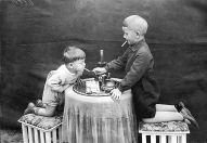 1928. Due bambini inginocchiati ai lati di un tavolo che fumano indisturbati