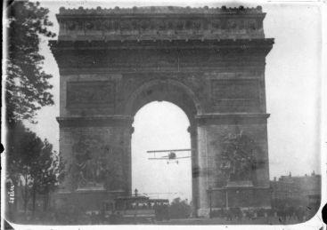 """Charles Godefroy porta il suo Nieuport 11 """"bébé"""" attraverso l'Arco di Trionfo a Parigi il 7 Agosto 1919"""