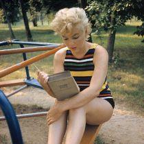 """Marilyn Monroe legge """"Ulysses"""" di James Joyce in un parco giochi, intorno al 1955. Fotografia di Eve Arnold"""