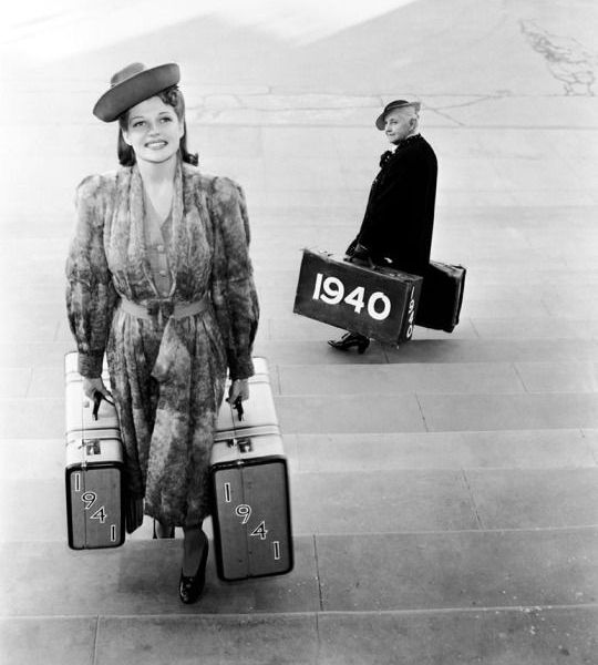 Una giovane Rita Hayworth passa al nuovo anno con un paio di valigie '1941' e incrocia lo scrittore Quentin Crisp con un paio di valigie '1940' che se ne va, 1 gennaio 1941 Getty Images/The John Kobal Foundation