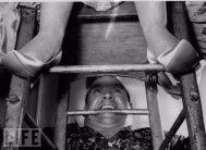 1959. Butty Sugroe utilizza i denti per sostenere la cantante irlandese Bridie Gallagher seduta su una sedia dopo la performance al London Palladium