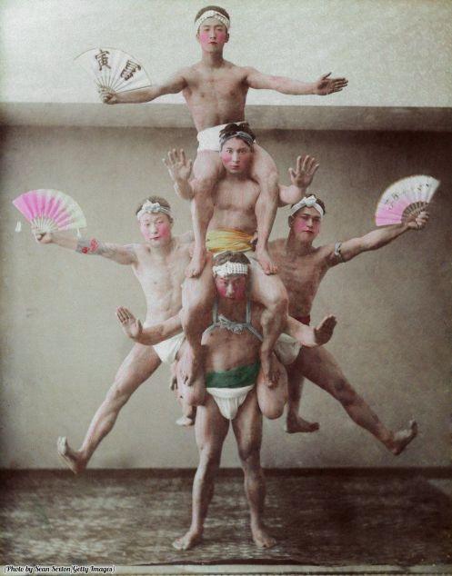 Lottatori giapponesi effettuano una prodezza acrobatica per i fan, circa 1890. Fotografia di Stillfried & Andersen