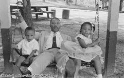 Martin Luther King Jr su un'altalena con la figlia Yolanda e il figlio Martin in un parco divertimenti, 1960