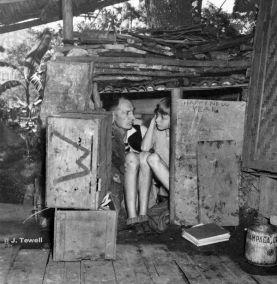 Padre e figlio si riparano durante il bombardamento giapponese di Santo Tomas, Manila, Filippine 1945