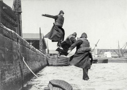 Poliziotti testano i giubbotti di salvataggio saltando in acqua a West India Docks. 1930