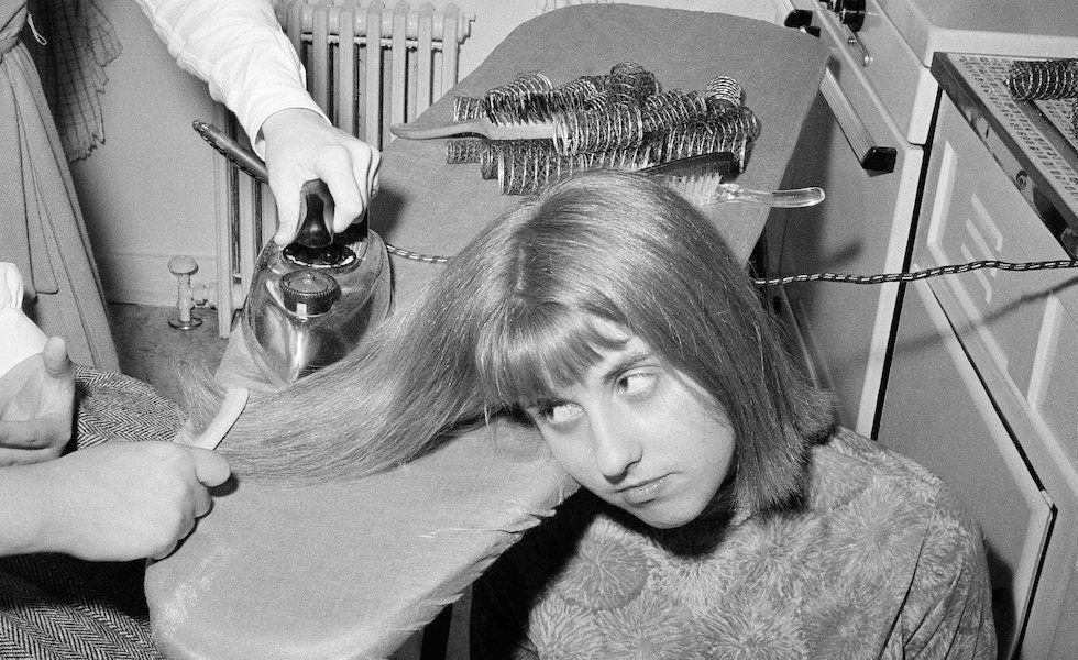 Una ragazza quattordicenne americana si fa allisciare i capelli con un ferro da stiro (1964)