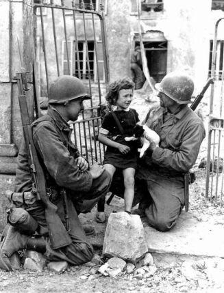 Due soldati americani cercano di confortare una bambina con un cucciolo. Seconda guerra mondiale, 1944