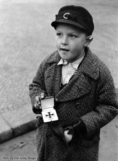 Un orfano tedesco cerca di vendere la Croce di ferro del padre in cambio di sigarette a Berlino, 1945