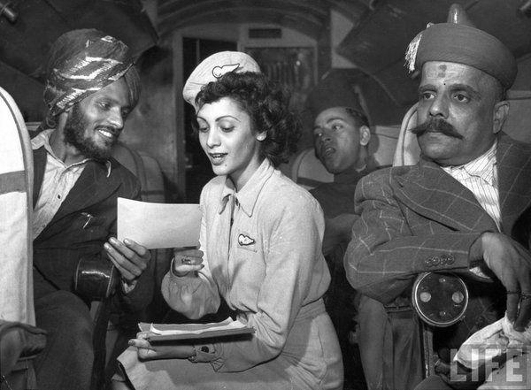 Assistente di volo della Air India che mostra il rapporto volo a un passeggero durante il viaggio Delhi-Bombay, 1946