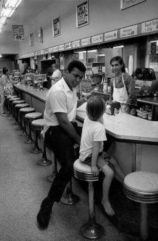 Muhammad Ali con un giovane fan in una tavola calda, Florida, 1970. Fotografia di Danny Lyon