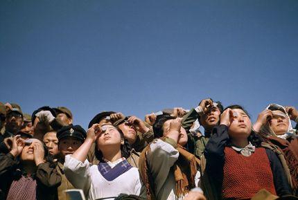 Persone che guardano un'eclissi solare attraverso il vetro o pellicola a Rebun Island in Giappone, marzo 1949