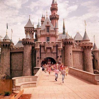 Bambini corrono oltre il cancello del Castello della Bella Addormentata nel giorno di apertura di Disneyland, nel 1955