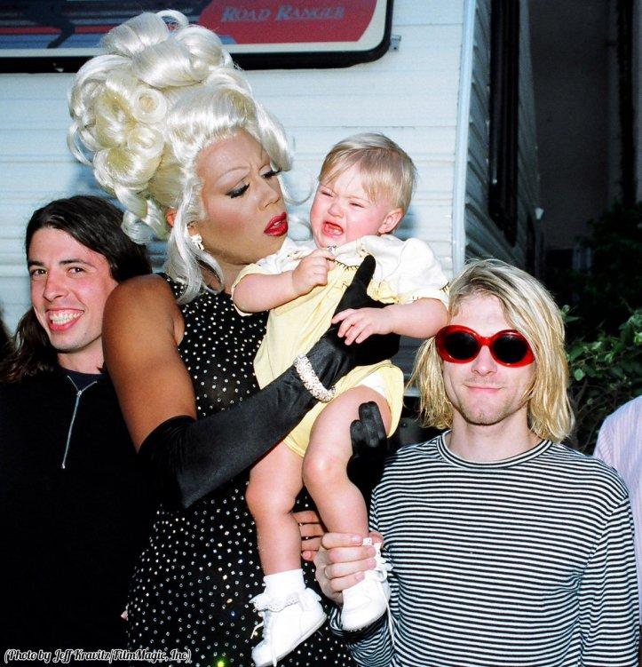 Dave Grohl e Kurt Cobain sorridono mentre RuPaul cerca di consolare Frances Bean, 1993