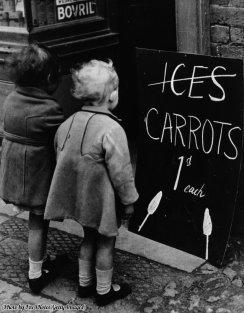 Due bambine che leggono una tavola che pubblicizza carote vere anziché ghiaccioli alla carota, 1941. Le carenze di guerra hanno reso tali sostituzioni una necessità
