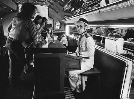 Elton John suona al piano bar del suo aeroplano privato, 1976