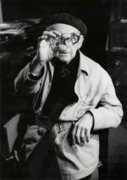 Man Ray con la sua lente di ingrandimento 'verre Laurent' nel suo studio, Parigi, 1969-1974 - Fotografia di Arnold Crane