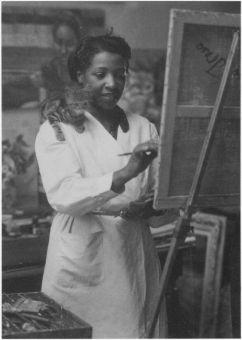 Loïs Mailou Jones dipinge nel suo studio di Parigi nel 1937 o nel 1938, con il gattino che controlla dalla sua spalla
