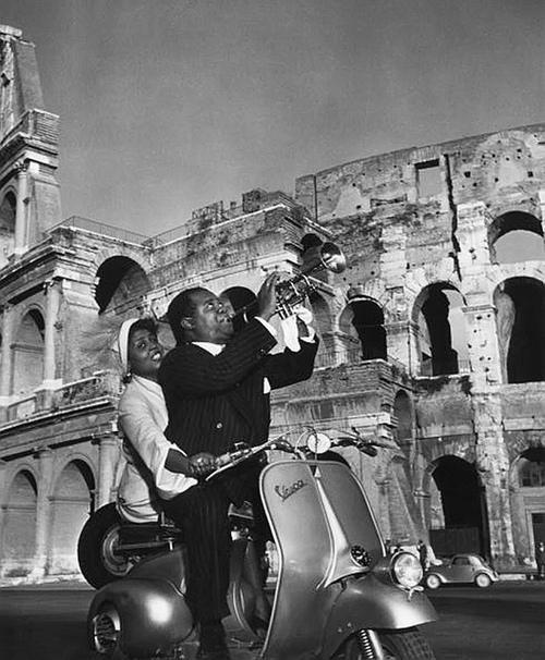 Lucille prende il controllo dello scooter mentre suo marito Louis Armstrong suona, Roma nel 1949. Fotografia di Slim Aarons